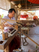An artisan carves the frame for their homemade paper parasols near the Myin Ma Hti Cave